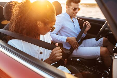 Image of young multiethnic couple man and woman wearing seat belts while driving convertible stylish car by seaside