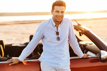 Photo of brunette caucasian man looking at cmera while standing by convertible car on beach at sunrise Imagens