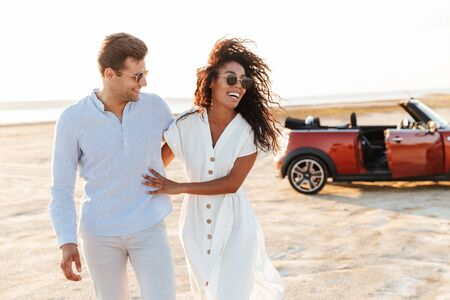 Photo of adorable multiethnic couple man and woman smiling together while walking by car on beach