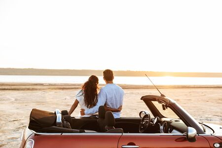 Photo from back of romantic multiethnic couple man and woman hugging together while standing by car on beach Standard-Bild