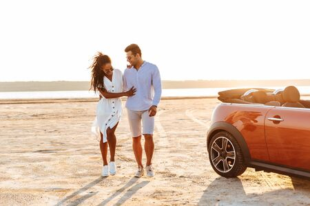 Photo of elegant multiethnic couple man and woman smiling together while walking by car on beach