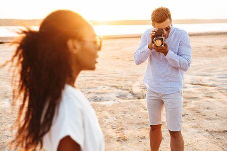 日没時に海辺を歩く美しい女性ながらレトロなカメラで写真を撮る白人男性の画像