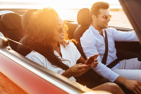Beautiful smiling young multiethnic couple riding in a convertible, holding mobile phone Banco de Imagens