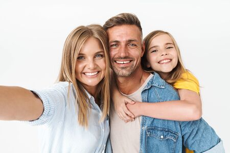 Image of amusing caucasian family woman and man with little girl smiling and taking selfie photo together isolated over white background