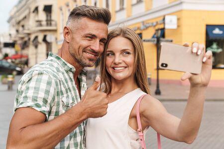 Foto de la joven pareja feliz en ropa de verano sonriendo y mostrando el pulgar hacia arriba mientras toma una foto selfie en las calles de la ciudad Foto de archivo