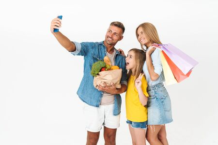 Cheerful family wearing casual outfit standing isolated over white background, shopping for groceries together, carrying bags, taking a selfie Stockfoto