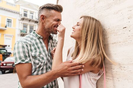 Image of lovely blonde couple in summer clothes smiling and flirting together while standing against wall on city street Фото со стока - 130007679