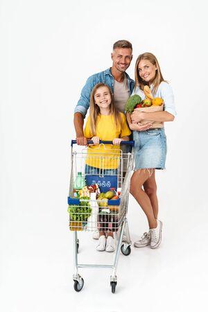 Toute la longueur d'une famille joyeuse portant une tenue décontractée isolée sur fond blanc, faisant l'épicerie ensemble, portant des sacs et un chariot Banque d'images