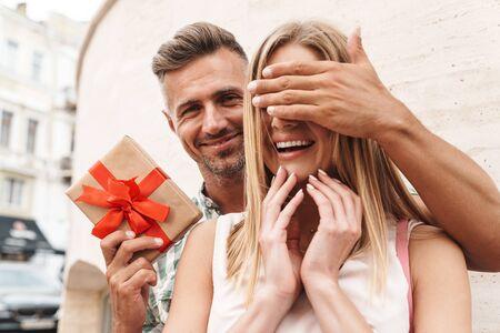 Imagen de la encantadora pareja emocionada en ropa de verano sonriendo y sosteniendo la caja presente juntos mientras está de pie contra la pared en las calles de la ciudad