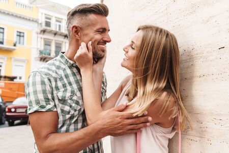 Image of attractive blonde couple in summer clothes smiling and flirting together while standing against wall on city street Фото со стока - 130007775