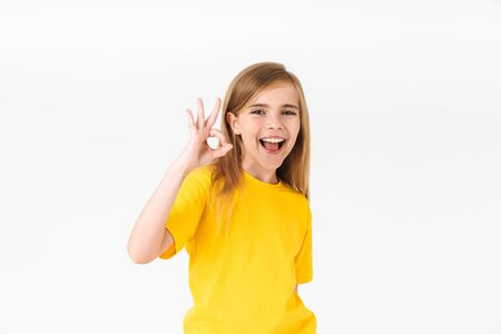 Portrait of happy blonde summer girl wearing casual t-shirt smiling and showing ok sign isolated over white background Stock Photo