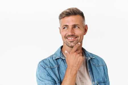 Photo of unshaved guy in denim shirt smiling and looking aside at copyspace isolated over white background