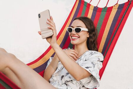 Image of a cheerful smiling young beautiful woman at the beach posing on a hammock take a selfie by mobile phone. Reklamní fotografie