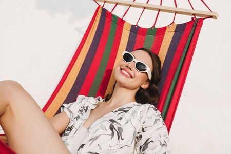 Image of a happy young beautiful woman at the beach posing on a hammock. Reklamní fotografie