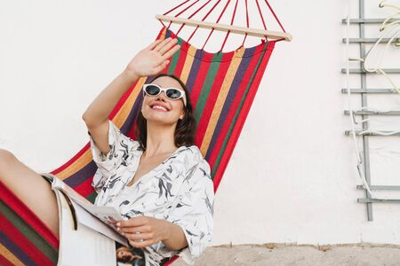 Image of a happy cheery smiling young beautiful woman at the beach posing on a hammock reading magazine waving to someone.