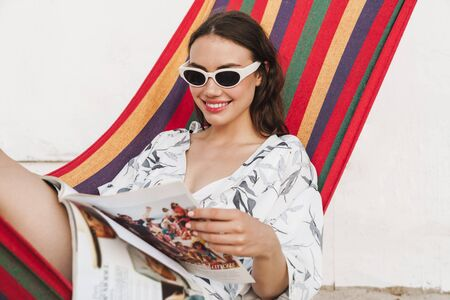 Image of a happy positive pleased smiling young beautiful woman at the beach posing on a hammock reading magazine. Reklamní fotografie