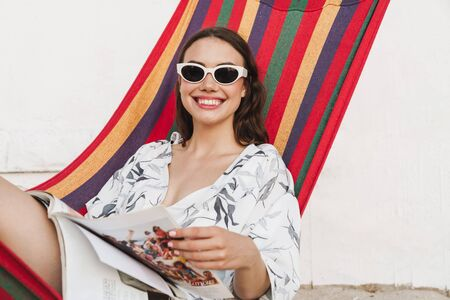 Image of a cheerful pleased smiling young beautiful woman at the beach posing on a hammock reading magazine.