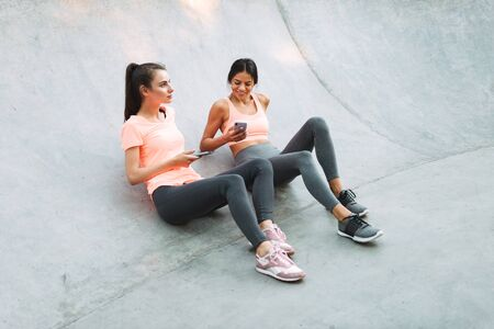 Image of pleased fitness women in sportswear smiling and holding cellphones together while sitting on concrete sports ground