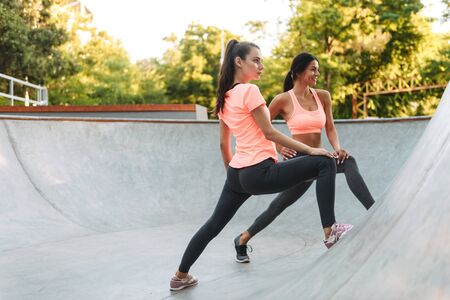 Image of athletic caucasian women in sportswear doing exercises on concrete sports ground