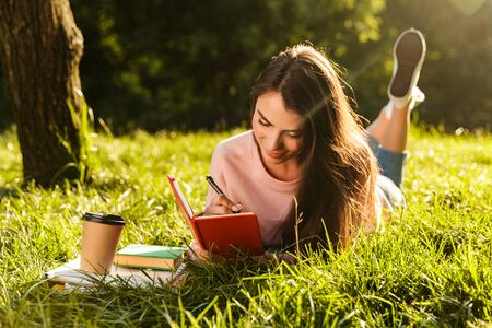 Image of pretty brunette woman smiling and writing down notes in diary while lying at grass in green park on sunny day