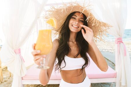 Photo of pretty brunette woman in straw hat and swimsuit drinking orange juice on beach bed in morning at summer resort