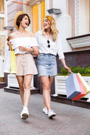 Image of a happy laughing optimistic happy young girls friends walking by street outdoors holding shopping bags.