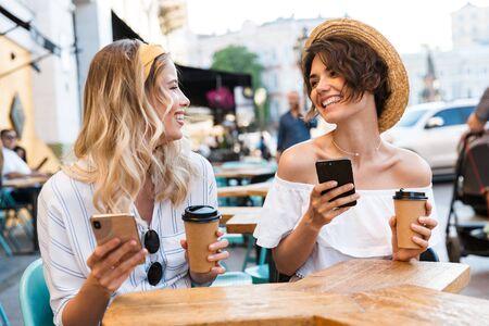 Zdjęcie szczęśliwych młodych optymistycznych przyjaciół dziewcząt siedzących na świeżym powietrzu w kawiarni picia kawy za pomocą telefonów komórkowych.