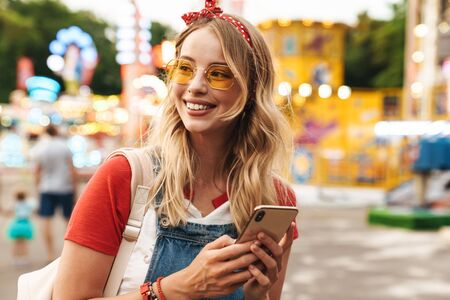 Image of a smiling young cheery blonde woman in amusement park using mobile phone. Stock Photo