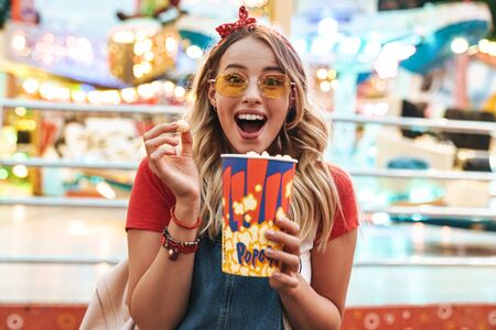 Image of sweet blonde woman wearing girlish clothes smiling and holding popcorn while walking in amusement park