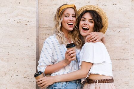 Image of a happy smiling positive young girls friends posing outdoors drinking coffee hugging. Stock Photo