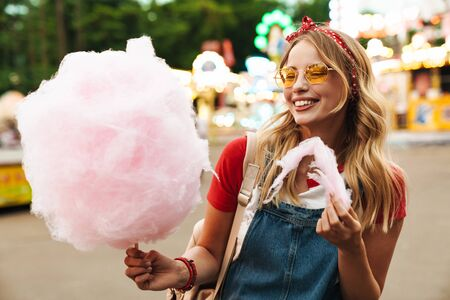 Image of happy blonde woman wearing girlish clothes eating sweet cotton candy while walking in amusement park Stock fotó