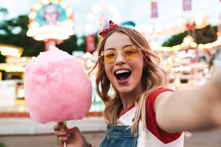 Image of excited blonde woman wearing girlish clothes holding sweet cotton candy while taking selfie photo at amusement park