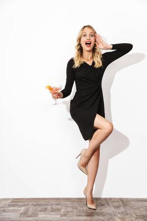 Portrait d'une jolie jolie femme blonde vêtue d'une robe noire isolée sur fond blanc, tenant un cocktail, posant