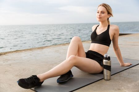 Image of relaxed woman wearing tracksuit resting and sitting with water bottle on mat while working out on pier near seaside in morning