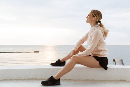 Image of attractive woman wearing tracksuit listening to music with earphones while sitting near seaside in morning