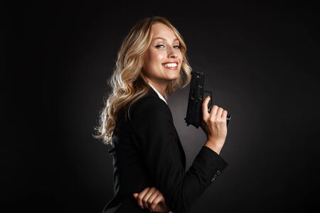 Portrait of a beautiful cheerful blonde haired business woman dressed in formal clothes standing isolated over black background, shooting with a gun