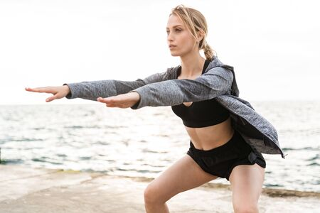 Image of seductive blonde woman wearing tracksuit doing exercise while working out on pier near seaside in morning