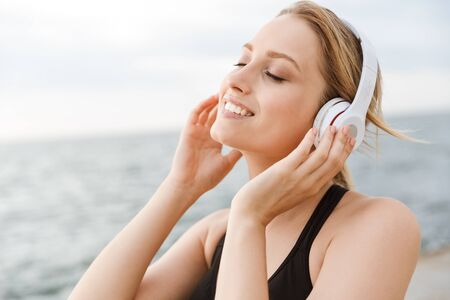 Image of happy beautiful woman wearing tracksuit listening to music with headphones near seaside in morning 写真素材