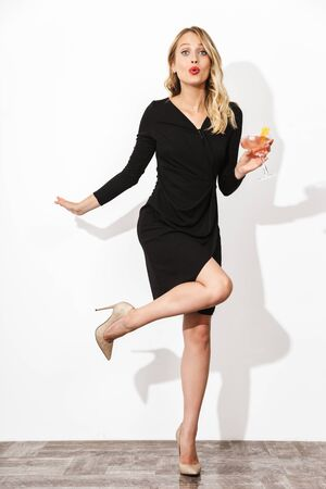 Full length portrait of an attractive lovely blonde woman dressed in black dress standing isolated over white background, holding a cocktail, posing Banco de Imagens