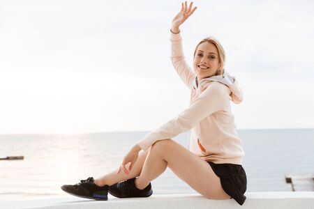 Image of young woman wearing tracksuit smiling and waving hand while sitting on pier near seaside in morning