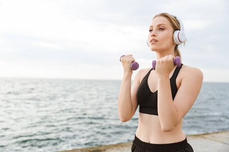 Image of serious cute woman wearing tracksuit using headphones while working out with dumbbells on pier near seaside in morning