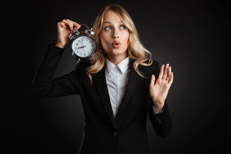 Portrait of a beautiful excited blonde haired business woman dressed in formal clothes standing isolated over black background, showing alarm clock, looking away Banque d'images - 130066656