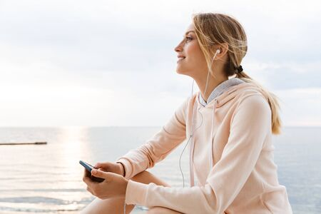 Image of pleased woman wearing tracksuit listening to music with cellphone and earphones while sitting near seaside in morning 版權商用圖片