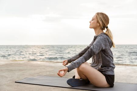 Image of blonde relaxed woman wearing tracksuit sitting with zen gesture while meditating on yoga mat near seaside in morning 写真素材