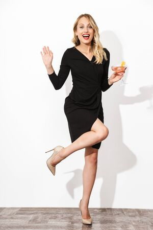 Full length portrait of an attractive lovely blonde woman dressed in black dress standing isolated over white background, holding a cocktail, posing Banco de Imagens - 130066688