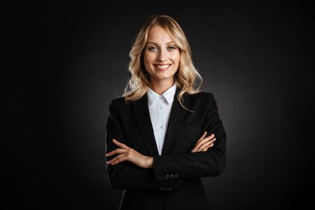 Portrait of a beautiful cheerful blonde haired business woman dressed in formal clothes standing isolated over black background, arms folded