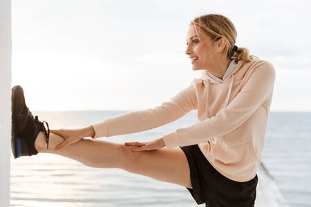 Image of smiling young woman wearing tracksuit stretching her leg while working out on pier near seaside in morning Фото со стока