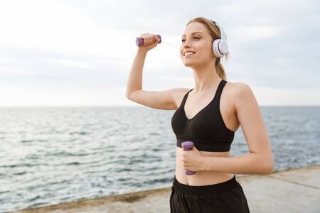 Image of smiling young woman wearing tracksuit using headphones while working out with dumbbells on pier near seaside in morning