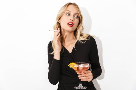 Portrait of an attractive blonde woman dressed in black dress standing isolated over white background, holding a cocktail, smoking a cigarette