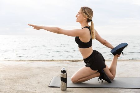 Image of smiling woman wearing tracksuit doing exercise on mat with water bottle while working out near seaside in morning Фото со стока